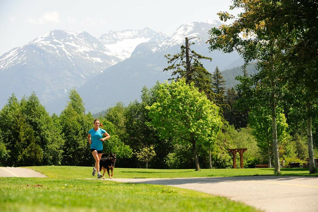 Woman running with her dog on the Valley Trail in Whistler BC.