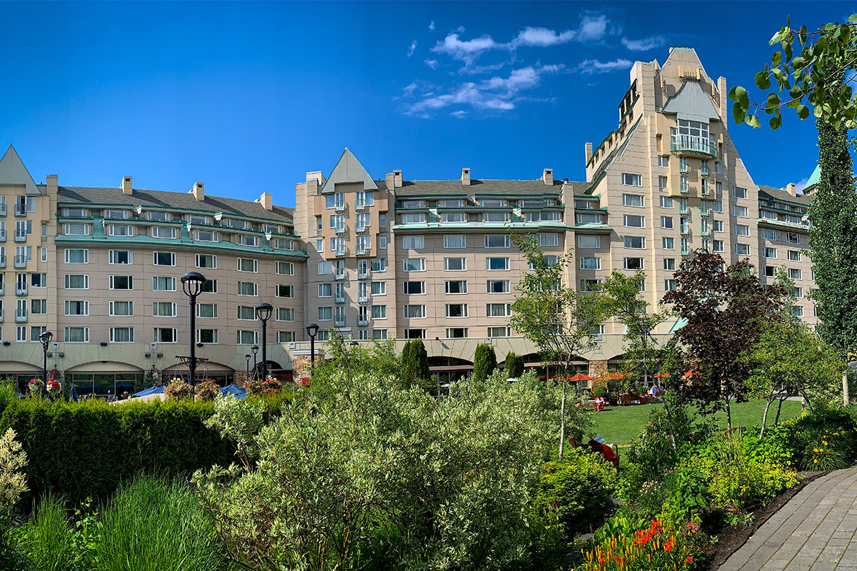 Fairmont Chateau Whistler summer exterior on a blue sky day.