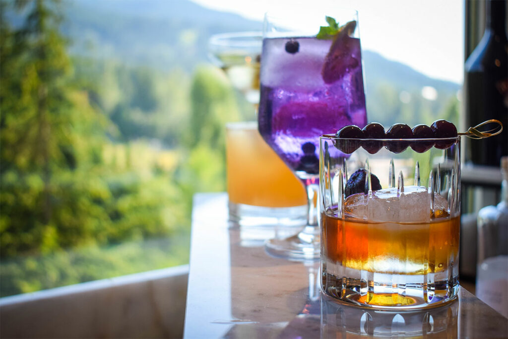 Cocktails in Fairmont Gold Lounge in Whistler with mountains behind.